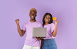 Leinwanddruck Bild - Online shopping. Millennial black couple with credit card and laptop making purchase via internet on lilac background