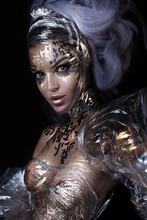 Close Up Portrait Of Young Graceful Nude Girl With Professional Black And Gold Hieroglyph Body Painting. Sexy Beautiful Expressive Woman With Garbage And Foil Transparent Dress And Lush Hairstyle
