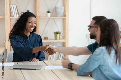 Obraz na plátně Real estate agent shaking hands with happy young couple in office at meeting