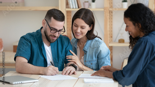 Fotografie, Obraz Smiling young family clients make purchase deal sign insurance contract at meeting with african american estate agent