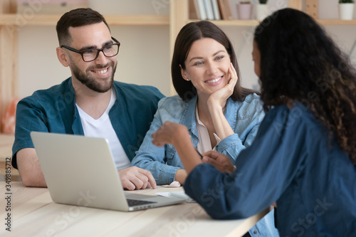Fototapeta Real estate agent consulting happy young couple about buying house rent purchase mortgage in office at meeting