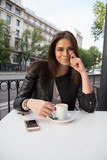 Fototapeta Kawa jest smaczna - Portrait Of Young Woman Having Coffee While Sitting At Sidewalk Cafe