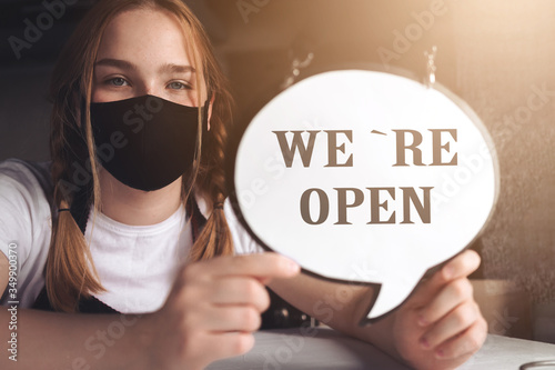 Obraz Coronavirus covid 19.Coffee shop woman owner with face mask, open after lockdown quarantine.End quarantine. Announcement we are open nv doors,  resumption shops, cafes,coffee houses, small businesses - fototapety do salonu