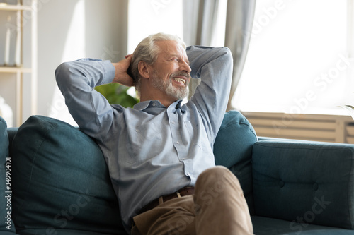 Fototapeta Relaxed happy grey haired mature old man enjoying free lazy weekend time on sofa. Tranquil calm peaceful smiling senior middle aged grandfather resting on couch alone, dreaming planning future. obraz