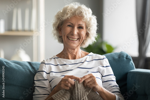 Fototapeta Happy elderly mature beautiful hoary grandmother relaxing on comfortable sofa, knitting warm sweater with woolen threads. Smiling middle aged woman enjoying free hobby weekend time alone at home. obraz