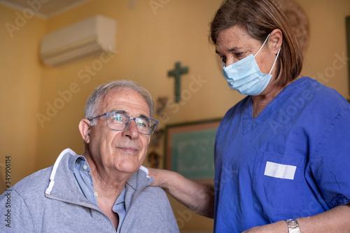 Infermiera con la mascherina facciale assiste anziano a domicilio seduto nel let Wallpaper Mural