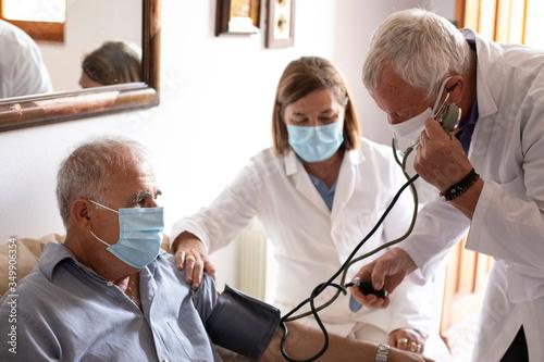 Fotomural Anziano con mascherina viene visitato da un medico a casa che gli prende la pres