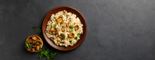 A Dish Of Italian Cuisine - Risotto From Rice And Mushrooms In A Brown Plate On A Black Slate Background. Top View. Flat Lay. Copy Space.