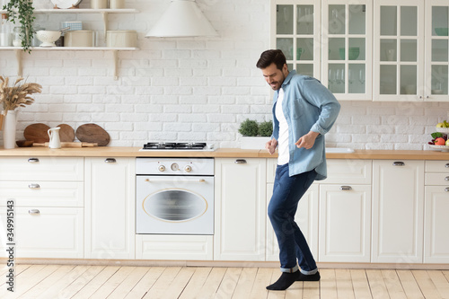 Obraz Happy millennial man enjoy leisure weekend dancing alone in bright modern design white kitchen, overjoyed young husband have fun entertain celebrate moving to new own home or apartment - fototapety do salonu