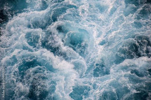 Fototapeta Seething waves covered with sea foam are illuminated by the light of the setting sun. Transparent. Dark blue. Blue. Background. Template. obraz
