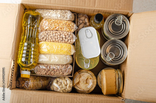 Valokuva Flat lay view at uncooked foods in carton box prepared for disaster emergency co