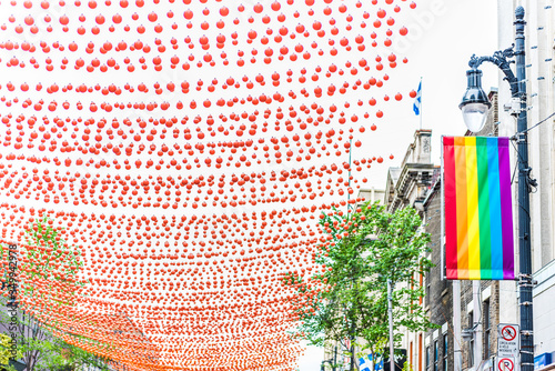 Montreal, Canada - May 26, 2017: Sainte Catherine street in Montreal's Gay Village in Quebec region with orange hanging decorations and lgbt flag