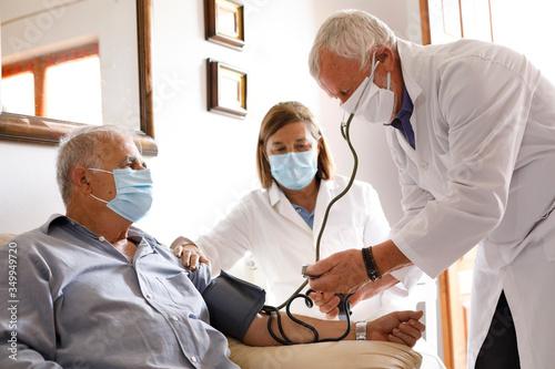 Fotografija Anziano con mascherina viene visitato da un medico a casa che gli prende la pres