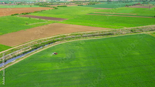 Fototapety, obrazy: Aerial view tractor spraying the chemicals on the large green field.
