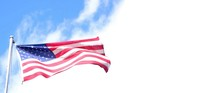 The American Flag Proudly Waving In The Wind Against A Blue And White Sky With Copyspace For Your Message To The Right Of The Flag