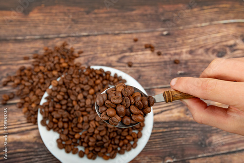 Fényképezés A man holds roasted coffee grains in a tablespoon on a background of a white plate and dark wood
