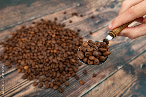 Vászonkép A man holds roasted coffee grains in a tablespoon on a background of a white plate and dark wood