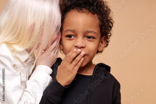Photo albino girl with pale skin and white hair color tells a secret in the ear of multiracial africanamerican boy