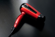 Red Hairdryer On A Black Wooden Table