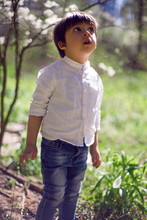 Caucasian Child Boy In A White Shirt Stands Outdoors
