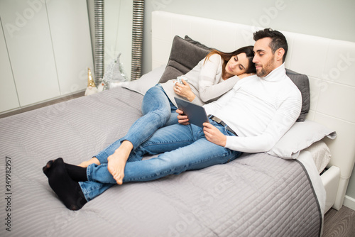 Fototapeta Couple watching a movie on their tablet while on the bed obraz na płótnie