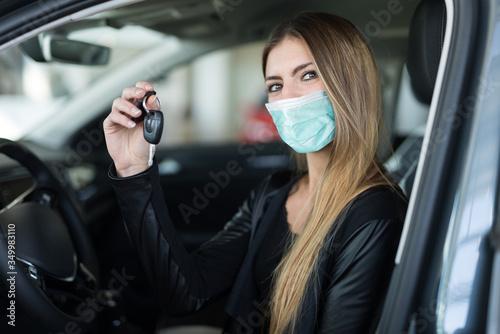 Fototapeta Masked woman showing the key of her new car in a car dealer saloon obraz