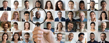 Male Employer Holding Magnifier In Hand Finding Unique Talent African Ethnic Job Candidate Choosing Among Many Lot Of Multiethnic People Different Faces Collage. Recruiting, Human Resources Concept.