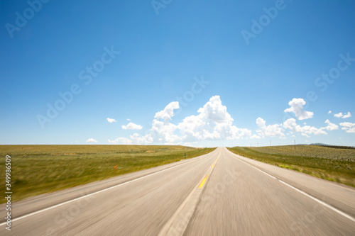 A point of view perspective of a vehicle traveling on a rural road with clouds and blue sky. - 349986509