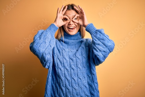 Fotografia, Obraz Young beautiful blonde woman wearing turtleneck sweater over yellow isolated background doing ok gesture like binoculars sticking tongue out, eyes looking through fingers