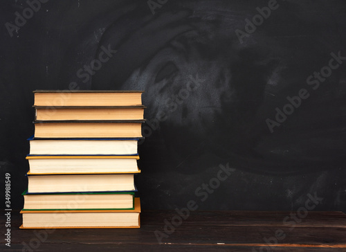 stack of various hardback books on the background of an empty black chalk board Fototapeta