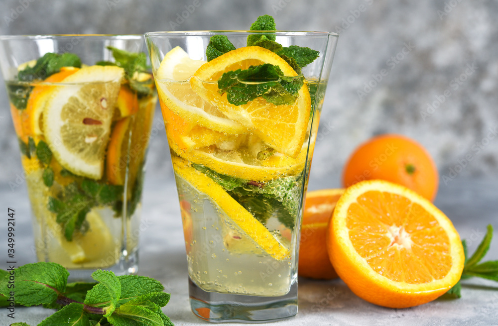 Fototapeta Classic summer cold drink - lemonade with orange, lemon and mint on a concrete background.