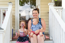 Young Mom Sitting On The Front Porch With Two Toddler Children On The 4th Of July