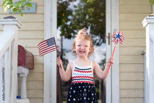 Vászonkép Happy toddler girl waving a flag and a pinwheel on the Fourth of July