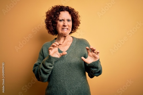 Middle age beautiful curly hair woman wearing casual sweater over isolated yellow background disgusted expression, displeased and fearful doing disgust face because of aversion reaction Canvas Print