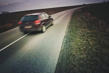 Blur Image Of Car On Road At Field Against Sky
