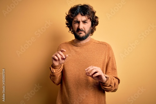 Photo Young handsome man with beard wearing casual sweater standing over yellow background disgusted expression, displeased and fearful doing disgust face because aversion reaction