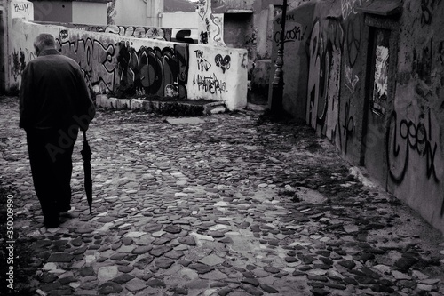 Obraz Full Length Rear View Of Senior Man With Umbrella Waking On Street Against Graffiti - fototapety do salonu