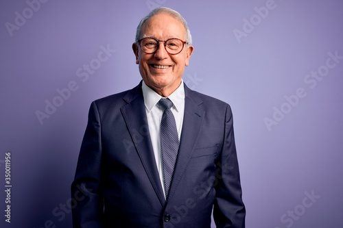 Grey haired senior business man wearing glasses and elegant suit and tie over purple background with a happy and cool smile on face Fototapet