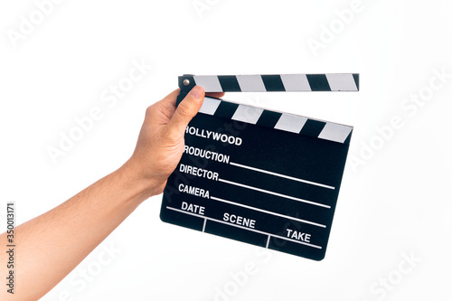 Fotografie, Obraz Hand of caucasian young filmmaker man holding clapboard over isolated white back