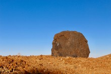 Huge Rust Red Volcanic Bomb Due To Iron Oxides, Lying Alone In The Middle Of A Field Of Stone Under A Cloudless Blue Sky Shot At The Golden Hour In The Teide National Park (Canary Islands, Spain)