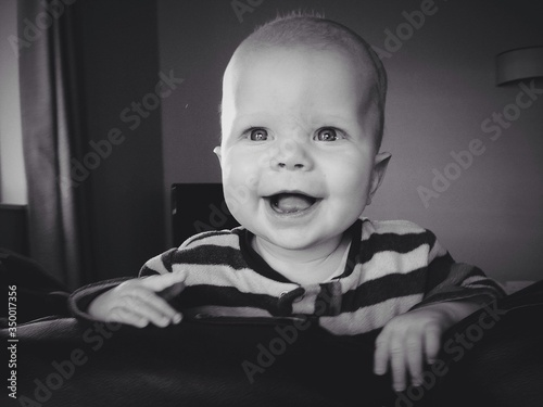 Cheerful Baby Looking Away While Leaning On Backrest Of Sofa At Home Canvas Print