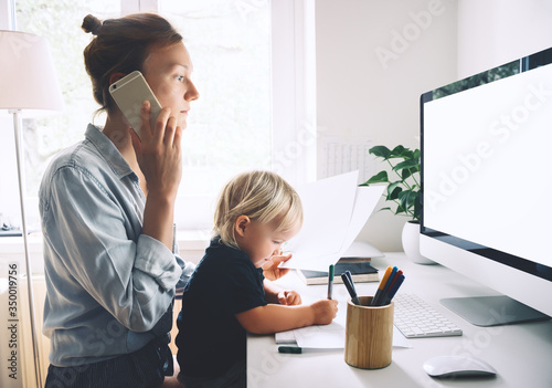 Obraz Mother working from home with little child. - fototapety do salonu