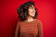 Leinwandbild Motiv Young beautiful curly arab woman wearing casual striped sweater standing over red background looking away to side with smile on face, natural expression. Laughing confident.