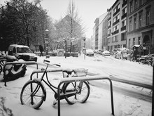 Snow Covered Bicycles With Buildings In Background