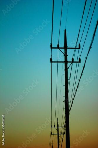 Fototapeta Low Angle View Of Electricity Pylon Against Blue Sky
