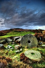 Millstones On Field Against Cloudy Sky