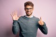 Young handsome man with beard wearing glasses and sweater standing over pink background showing and pointing up with fingers number six while smiling confident and happy.