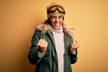 Young African American Afro Skier Girl Wearing Snow Sportswear And Ski Goggles Celebrating Surprised And Amazed For Success With Arms Raised And Eyes Closed. Winner Concept.