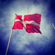 Low Angle View Of Danish Flag Against Cloudy Sky