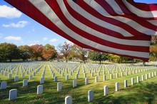 American Flag By National Cemetery Against Sky